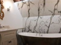 Traditional bathroom with bespoke furniture and hand finished copper leaf bath.