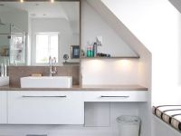 Twin countertop basins in this high gloss white en-suite bathroom. Corian countertop and light shelves. The LED lighting is switched by motion sensors.