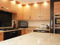 Contemporary light oak kitchen and high gloss bronze acrylic pull out storage. Curved island with breakfast bar.