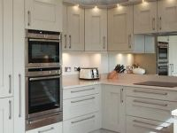 A contemporary Shaker fitted kitchen with NEFF appliances. Silestone worktops with drainer grooves and FRANKE sink. Mirror splashback.