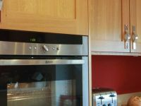 Silestone worktops with oak shaker kitchen cabinets. NEFF compact oven and warming drawer.